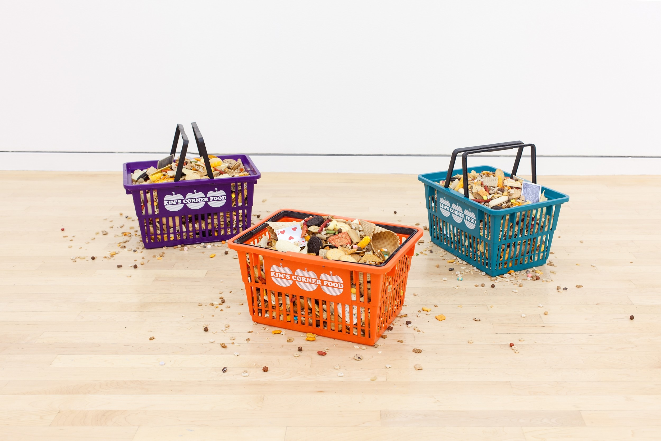 Earn like a dog, spend like a king, 2016 Screen printed plastic shopping baskets, unpackaged merchandise from Kim's Corner Food, 1371 W Estes Ave, Chicago, IL Installation view, Lake Cream, Block Museum, Evanston, IL, May–Jun 2016