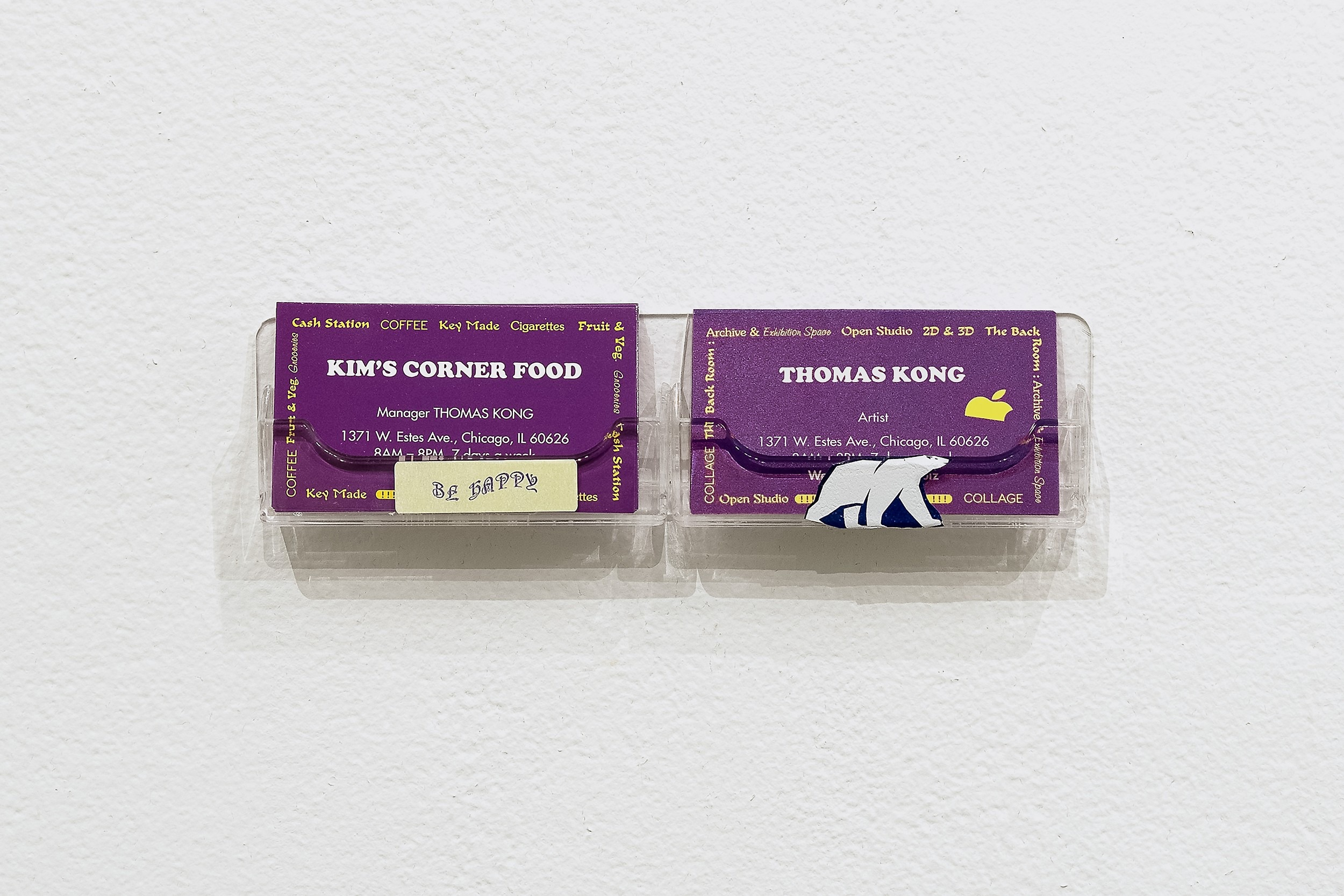 Thomas Kong/Dan Miller, Be Happy, 2015–19 Two-sided business cards, paper collage on acrylic business card holder, 2 x 8.2 x 0.75 inches Installation view, Coco Hunday Presents, Atlanta Contemporary, Aug–Dec 2019 Photo by Kasey Medlin